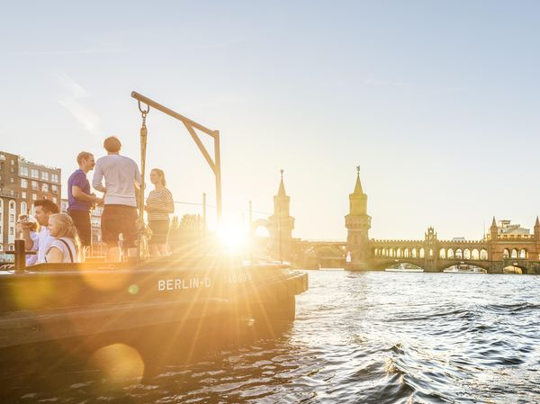A boat with several young people lies in the sunset in front of the Oberbaum bridge.