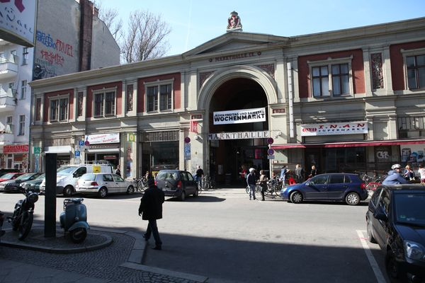 View over a street onto the Berliner Markthalle nine, in front of which some cars are parked.