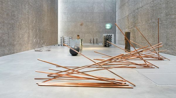 Art installation with golden metal rods in a large exhibition hall