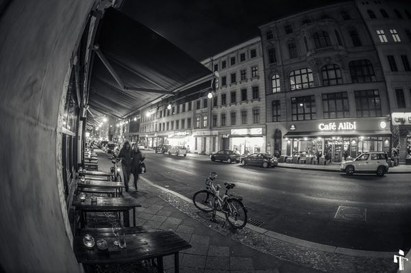 View into a Kreuzberger street at night with cafes and small tables in the foreground