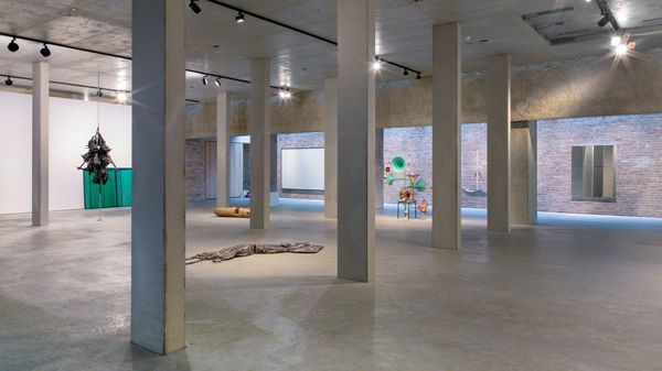 A large exhibition space in the König Galerie in Berlin with several concrete columns and some art objects in them.